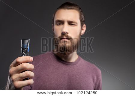 Cheerful guy with beard is thinking about shaving