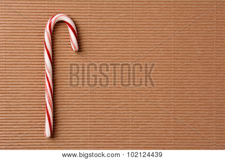 Overhead closeup view of a single candy cane on a sheet of corrugated cardboard. Horizontal format with copy space.