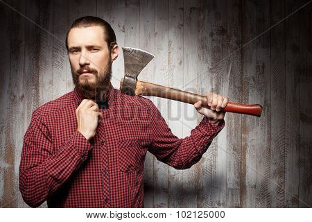 Handsome young bearded man is using axe