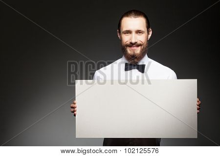 Cheerful young bearded man is presenting billboard