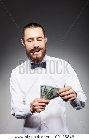 Handsome young hipster guy with cigarette and dollars