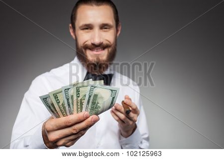Attractive young man with dollars is smoking