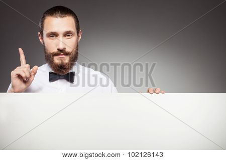 Handsome young man with beard is showing billboard