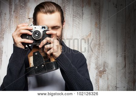Attractive young bearded man is photographing something