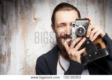 Cheerful young photographer with beard is making photos