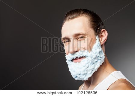 Attractive bearded young hipster guy is ready to shave