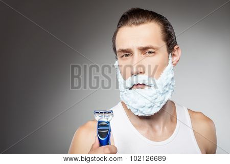 Cheerful young hipster guy is ready to shave beard