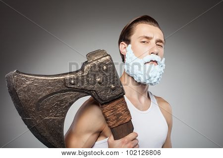 Cheerful young man is carrying axe during shaving