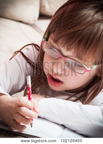 Little Girl Writing In Her Notebook