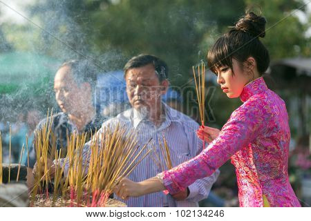 HO CHI MINH VILLE, VIETNAM, FEBRUARY 22, 2015 : A woman in traditional dress is inserting incense stick in the burning pot of the Vinh Nghiem pagoda in Ho Chi Minh (Saigon), Vietnam.