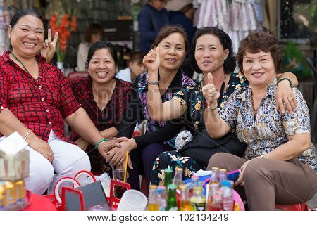 HO CHI MINH VILLE, VIETNAM, FEBRUARY 26, 2015 : A group of friendly vegetable sellers is posing in the street of Chinatown of Ho Chi Minh Ville, (Saigon), Vietnam.