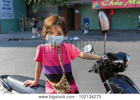 HO CHI MINH VILLE, VIETNAM, FEBRUARY 21, 2015 : A little girl wearing a face mask against pollution is ready to ride the motorbike of her father ! Ho Chi Minh, (Saigon), Vietnam.