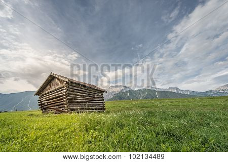 old wooden farm shed hut at green meadow and mountains