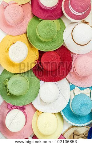 Variety Of Colored Straw Hats Hanging On A Wall