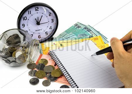 Hand with pen calculator clock and money on white background.