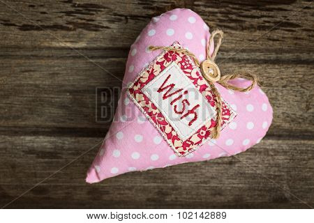.pink Soft Handmade Fabric Textile Heart With Word Wish On Wooden Background, Top View.