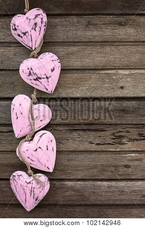 Pink Wooden Hearts On Old Brown Wooden Background