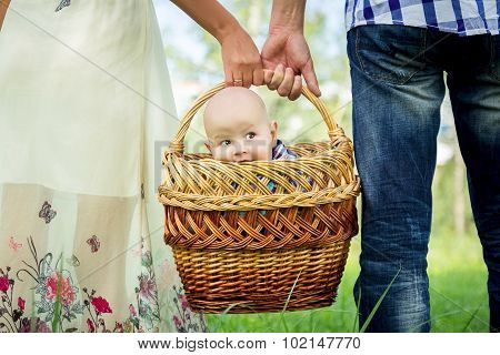 Man and woman holding basket with little boy