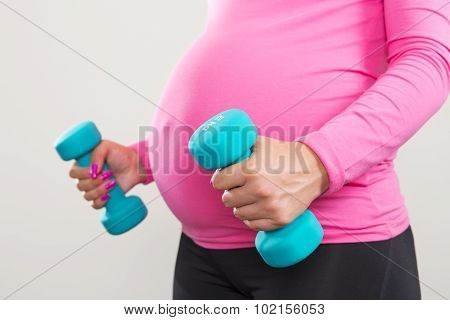 Pregnant woman exercising with training weights