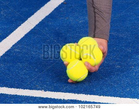 Tennis balls picked up by a ball kids hand on a blue artificial grass court