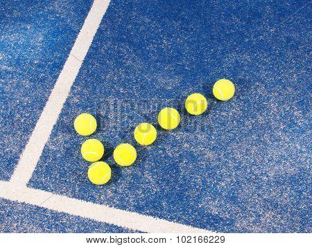 Tick symbol of Tennis balls a pristine blue artificial grass court