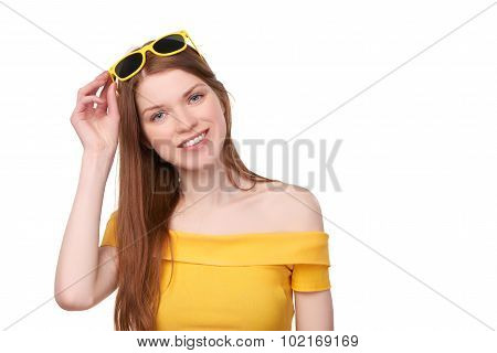 Smiling redheaded female in yellow top and sunglasses