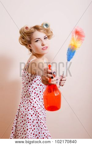 Sexy girl in curles pointing by spray bottle at camera