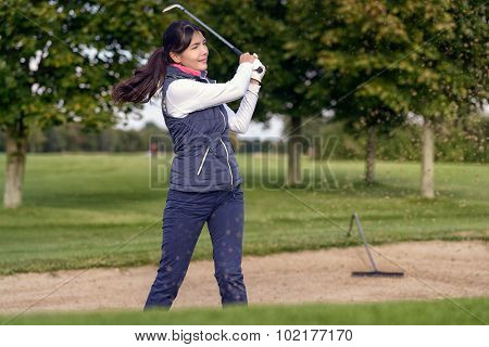 Woman Golfer Playing Out Of A Sand Bunker
