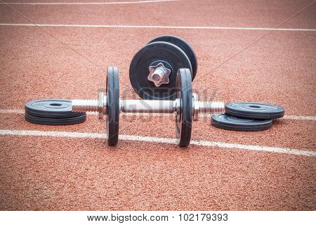 Dumbbells with weights on sports ground