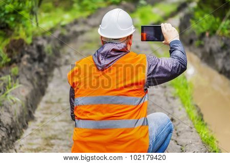 Forest officer filmed with tablet PC rutted forest road