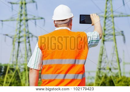 Electrical engineer filmed with tablet PC near high voltage power line
