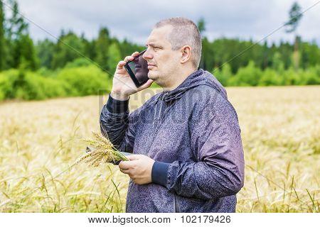 Farmer talking on cell phone near cereal field