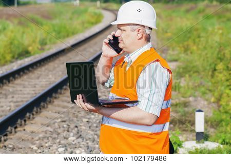 Railway Engineer with smartphone and laptop near railway
