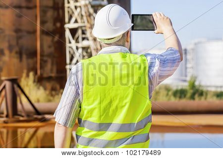 Engineer with tablet PC near to the tanks