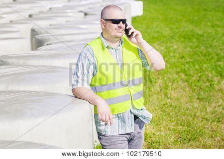 Farmer talking on smartphone near bales