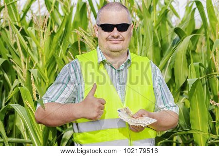 Farmer with money showing thumb up on corn field