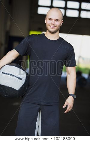 Smiling young man with med-ball at fitness gym