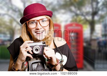 Girl in hipster glasses with vintage camera on UK street
