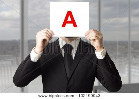Businessman In Suit Holding Up Sign With Letter A