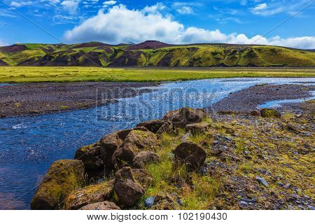 Picturesque basalt hills overgrown green grass and moss. On bottom of canyon many streams flow. Canyon Pakgil in Iceland