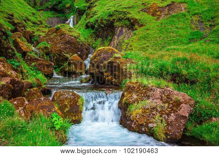 Iceland. Basalt mountains covered in green grass and moss. Gorgeous cascading waterfall from melting glacier
