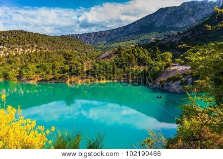 Smooth emerald green river water reflects the sky and wooded shore. Mountain canyon Verdon in the French Alps