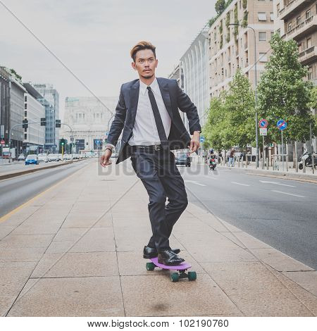 Young Handsome Asian Model Riding His Skateboard