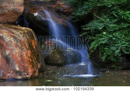 Fresh Water Flowing Over Rocks In A Pond