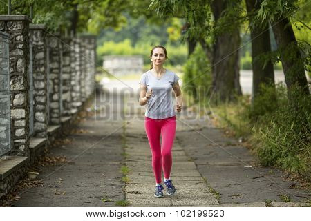 Young jogger girl running along the path in the Park.