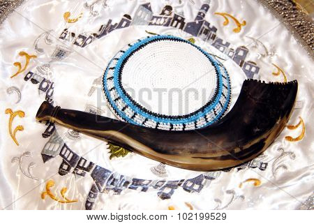 A yarmulke and shofar horn which traditionally blown over the Jewish holiday of Rosh Hashanah. A shofar is a horn that is used as a musical instrument for Jewish religious purposes. It is intimately connected with both Rosh Hashanah and Yom Kippur. The sh