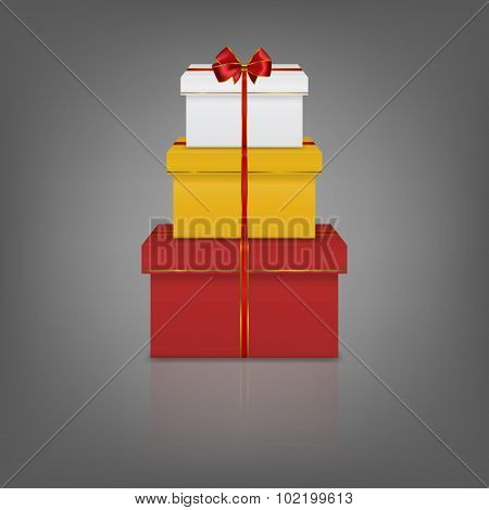 Stack of three realistic gift boxes with red ribbon and bow