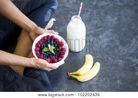 Above shot of a unrecognizable woman sitting on the floor with a bowl of berries, a bottle of almond milk and two bananas wearing a sportive outfit.
