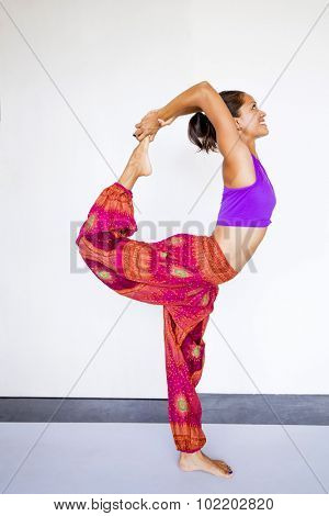Young beautiful woman wearing harem pants indoors, practicing a yoga pose (dancer's pose)