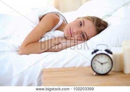 Woman can not sleep.Clock on the desk
